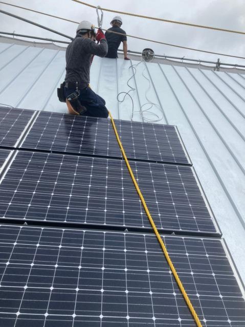 ソーラーパネルを設置する人